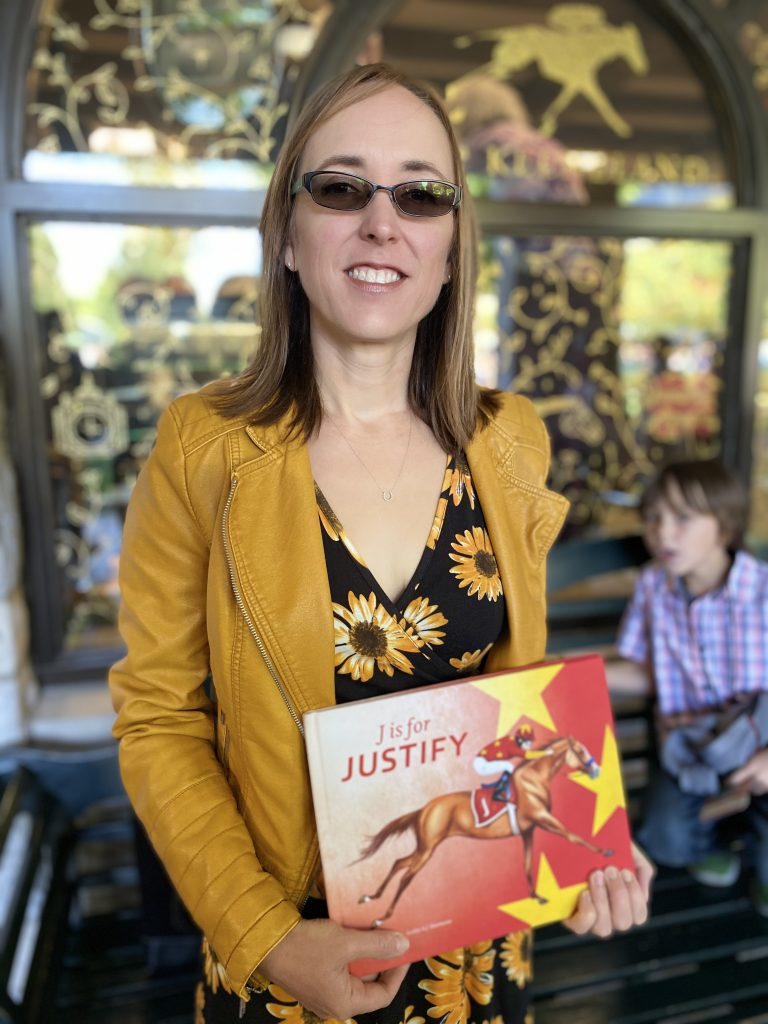 author/illustrator holding J is for Justify book in front of the Keeneland gift shop